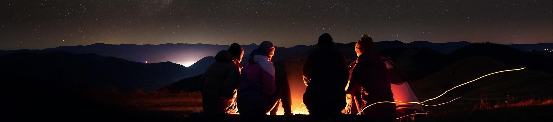 grupa przyjaciół przy ognisku podczas gwieździstej nocy banner